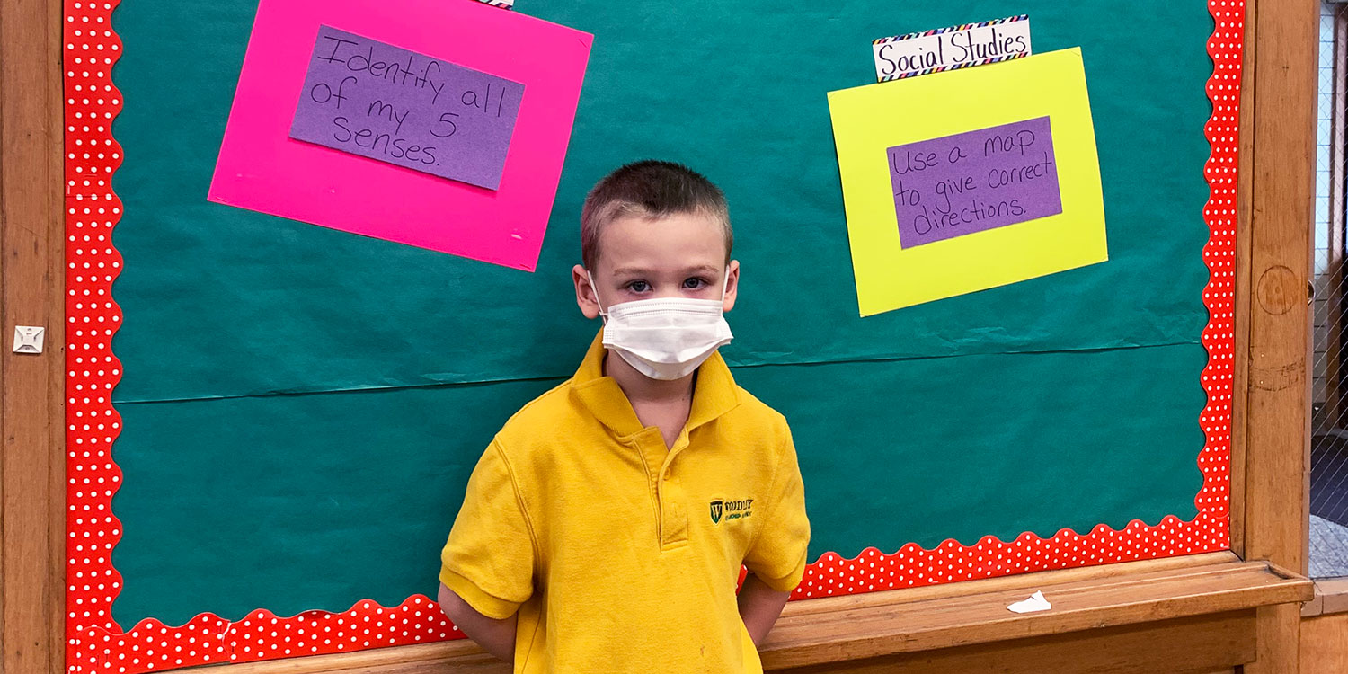 Elementary student standing in front of a classroom bulletin board.