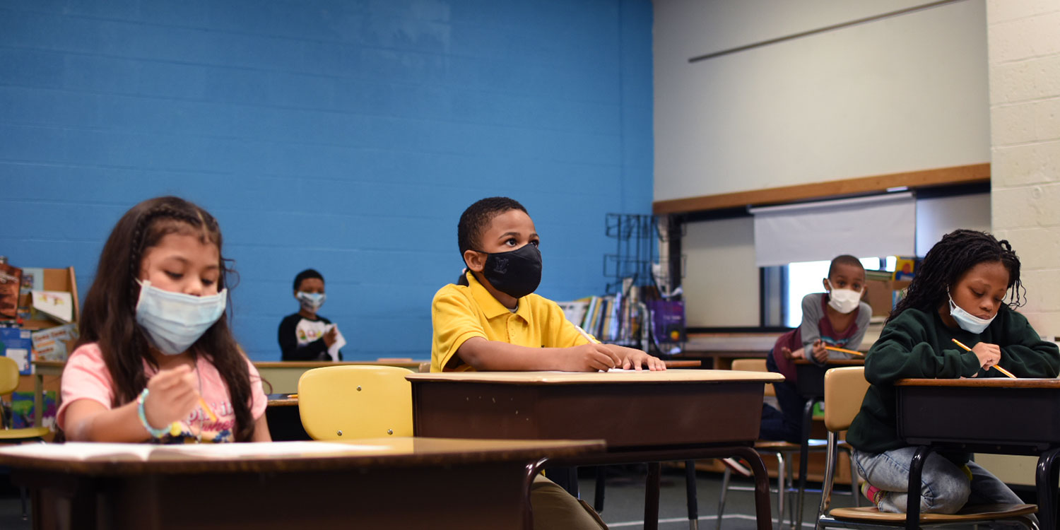 Masked elementary students sitting at their desks in a classroom.