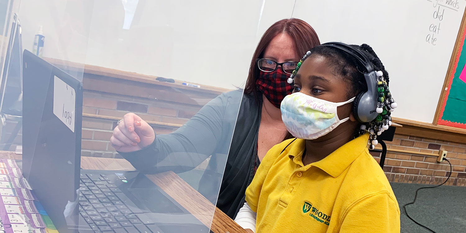 Masked student and teacher working on laptop at a desk.